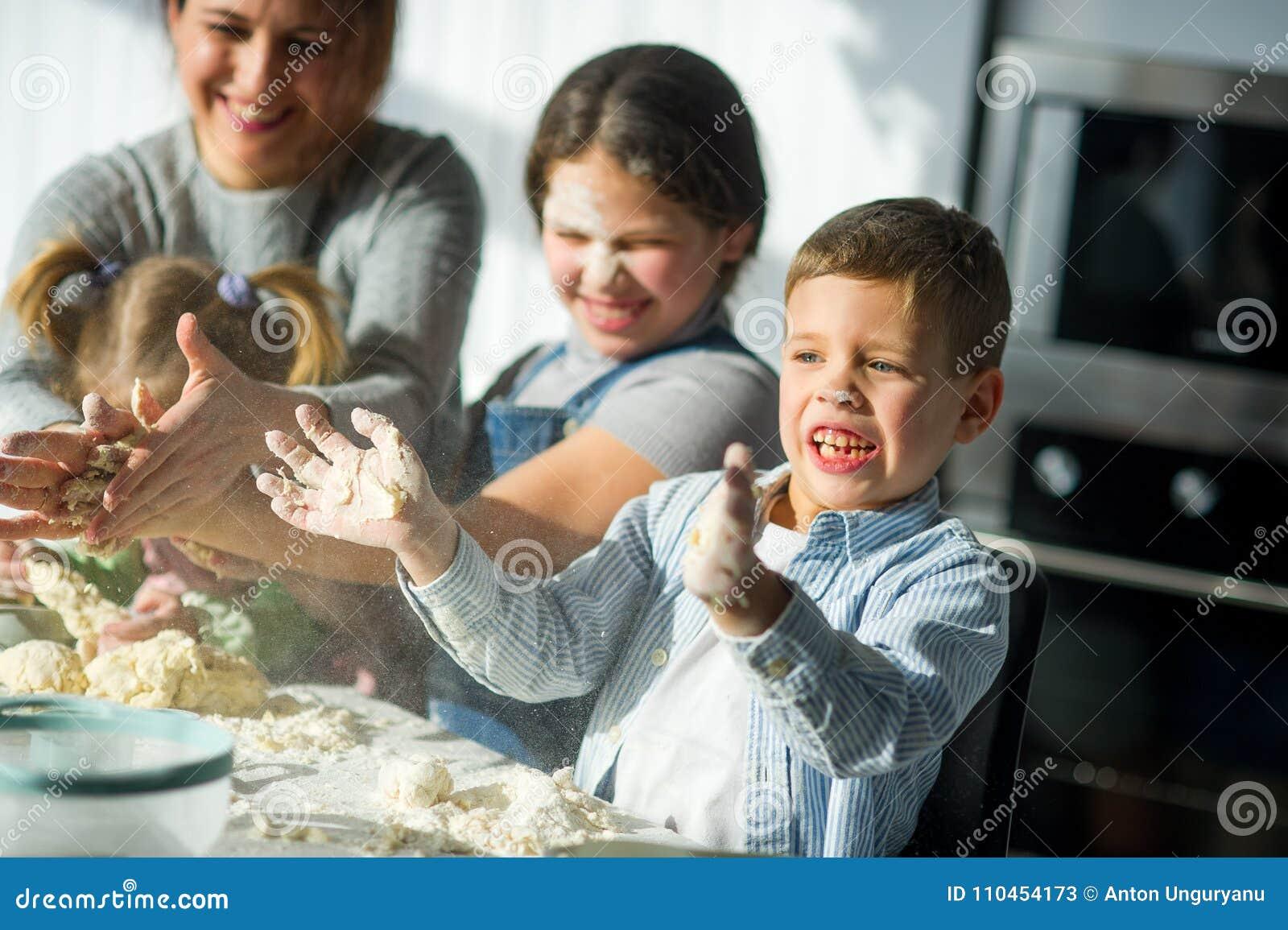 Modern och tre barn förbereder något från degen