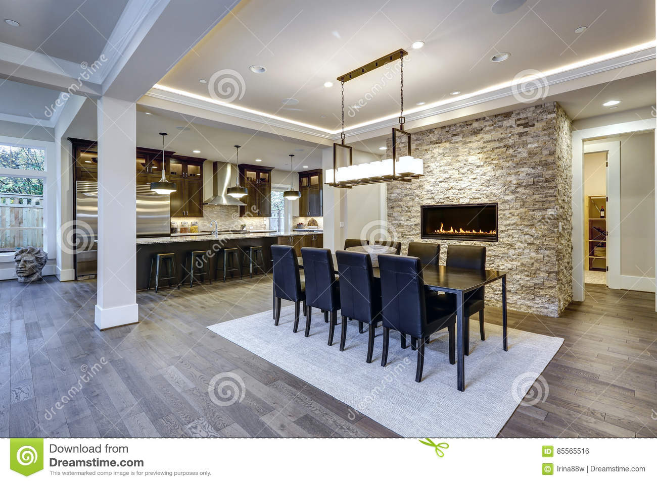 Modern Open Floor Plan Dining Room Design Accented With Stone Fireplace Wall Facing Black Table Lined Leather Chairs And Illuminated By