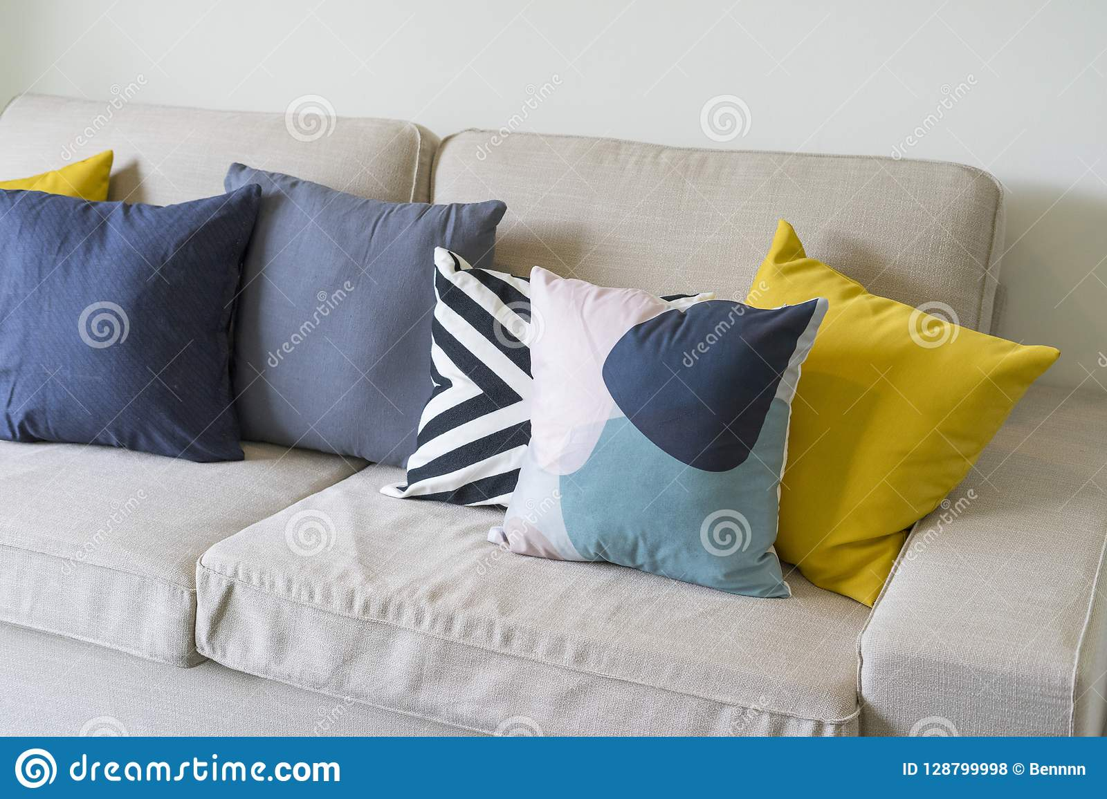 Modern Pattern Blue And Yellow Cushion On Grey Sofa Stock Photo
