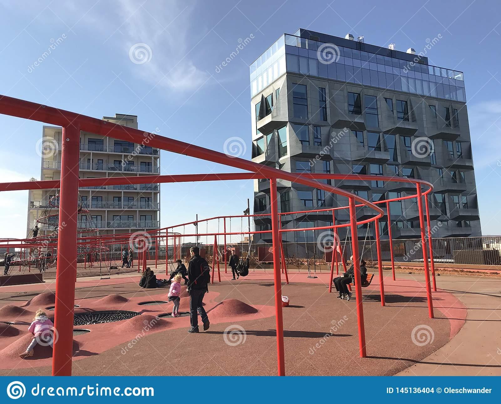 Modern playground with lots of activities and modern high rise buildings in the background.