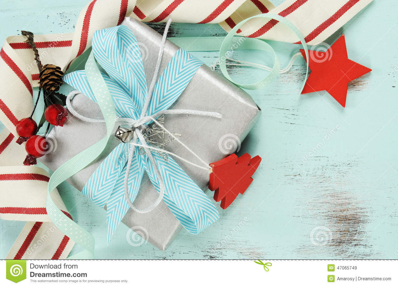 modern red and white christmas decorations on aqua blue wood background with silver gift closeup