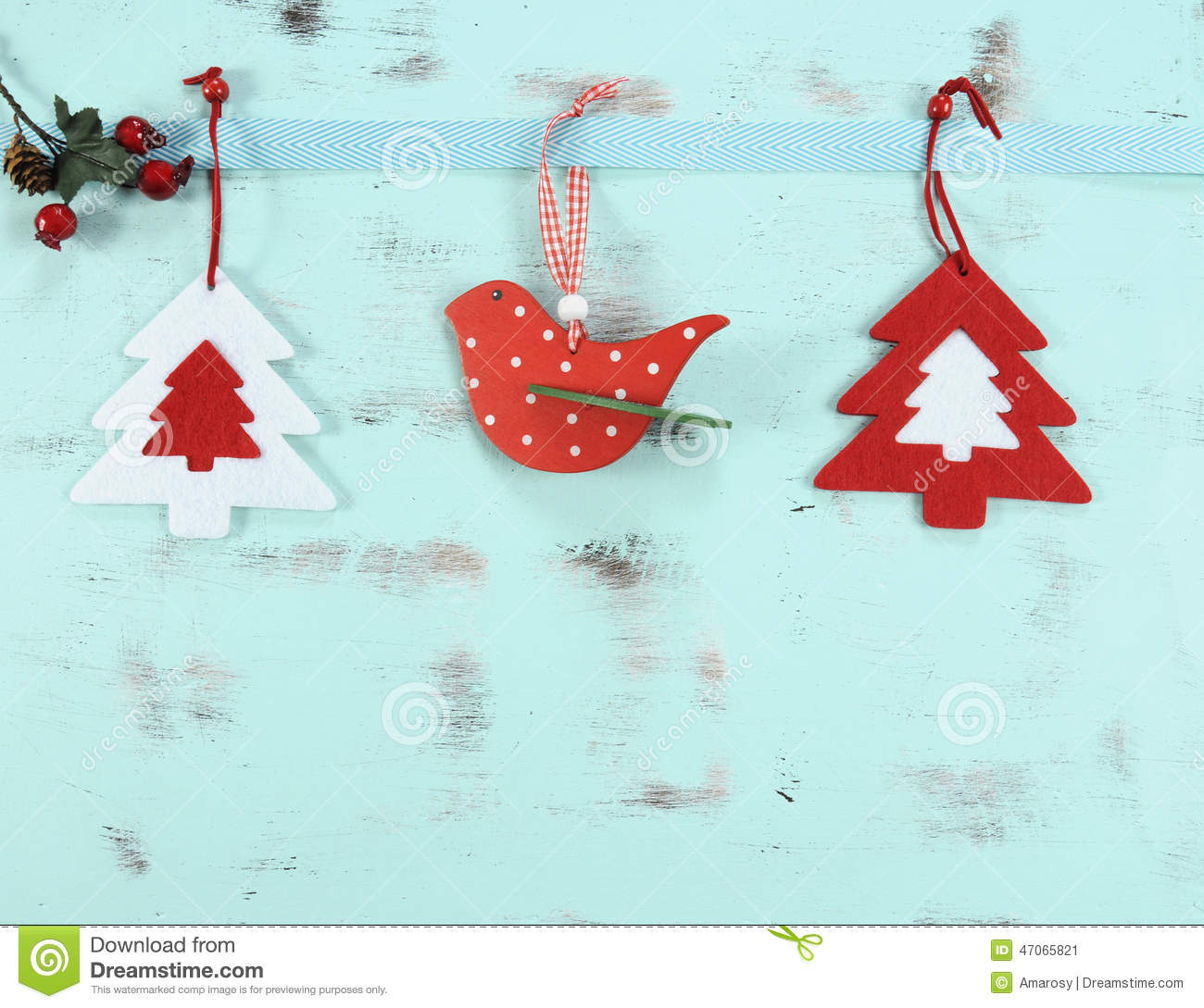 Modern red and white Christmas hanging bird and tree decorations on aqua blue wood background.