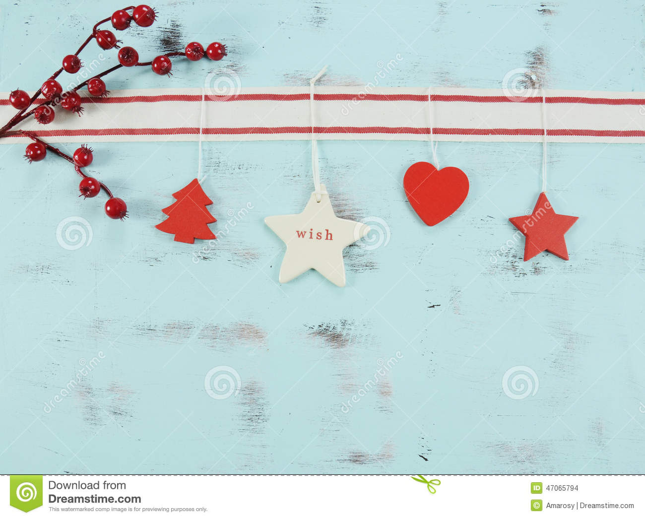 Modern red and white hanging Christmas decorations on aqua blue wood background.