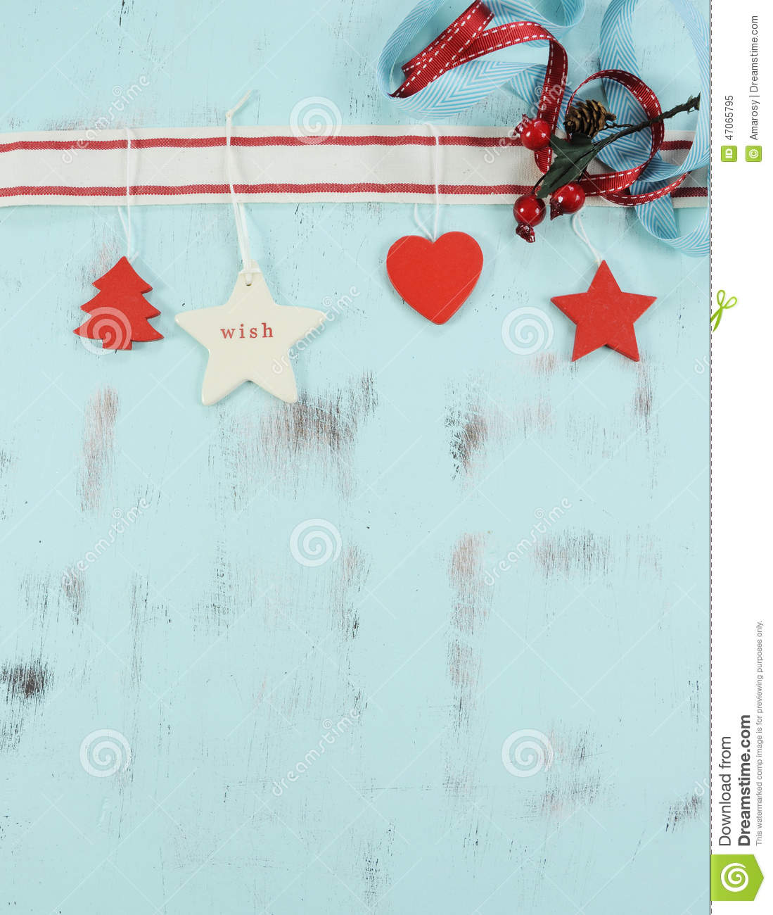 Modern red and white hanging Christmas decorations on aqua blue wood background. Vertical.