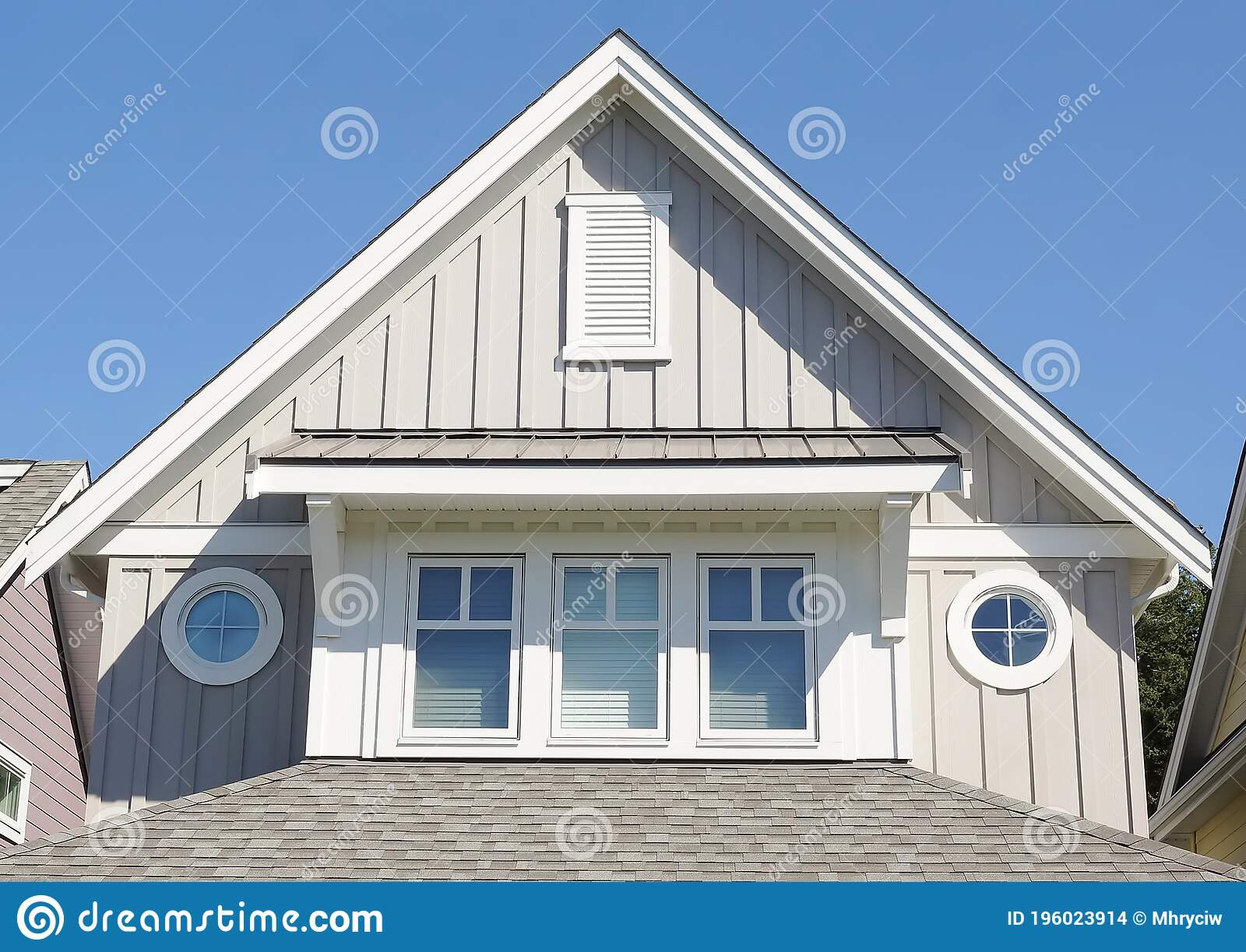 modern residential home exterior showing light gray painted board batten siding roof peaks round windows designer house front 196023914