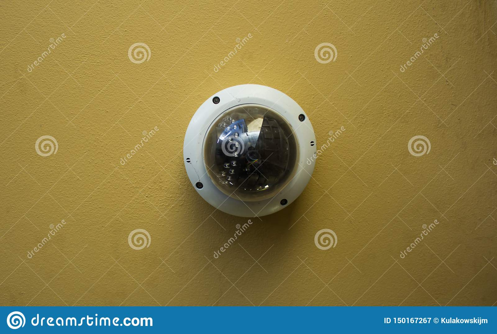 Modern round security camera on a yellow ceiling