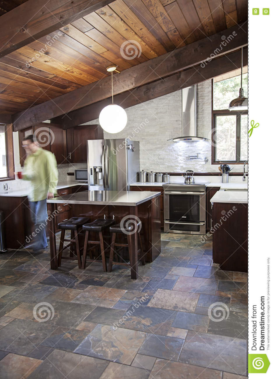 A Modern Kitchen With Slate Floor, Stainless Steel, White And Cherry  Finishes. Motion Blur Of Man Walking In Kitchen.