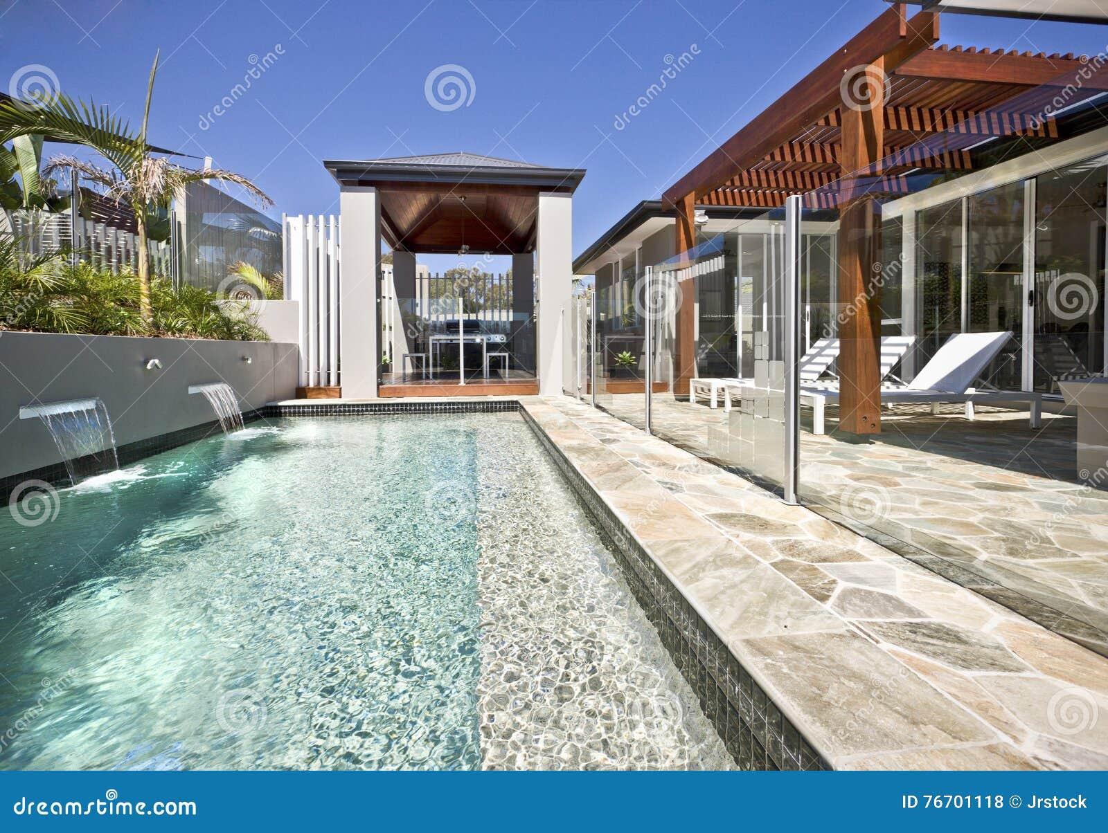Modern simbassängsida med den glass räkningen och träuteplatsen