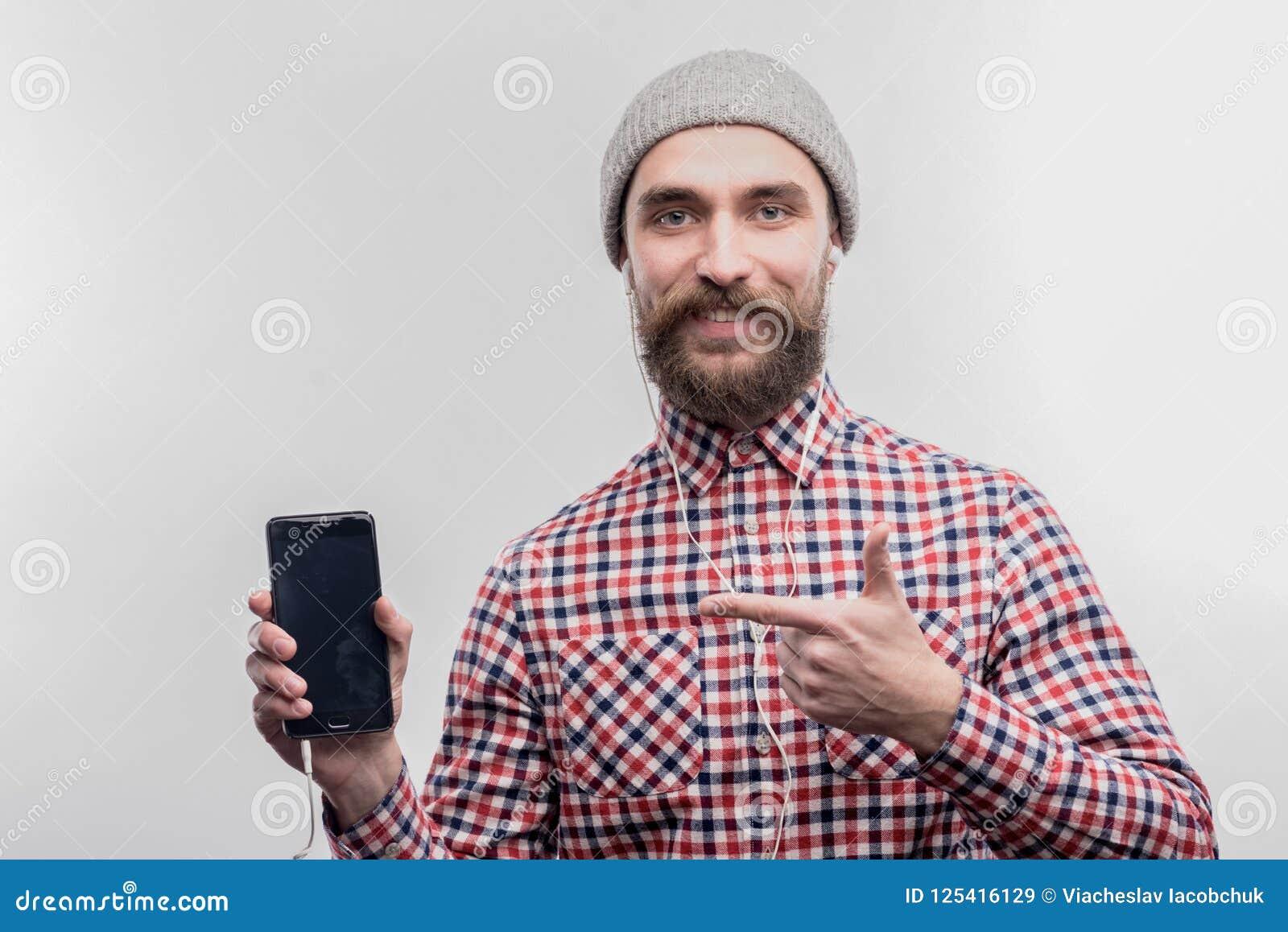 Modern skäggig mörkhårig man som lyssnar till hans favorit- musik i hörlurar