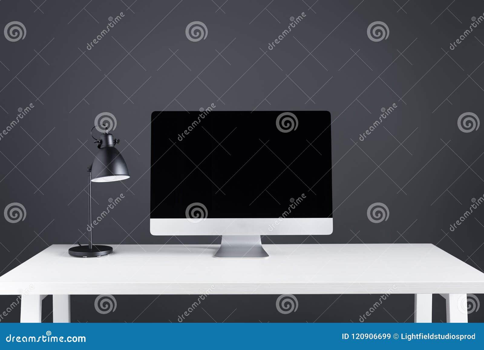 Modern skrivbords- dator med den tomma skärmen och lampan på tabellen