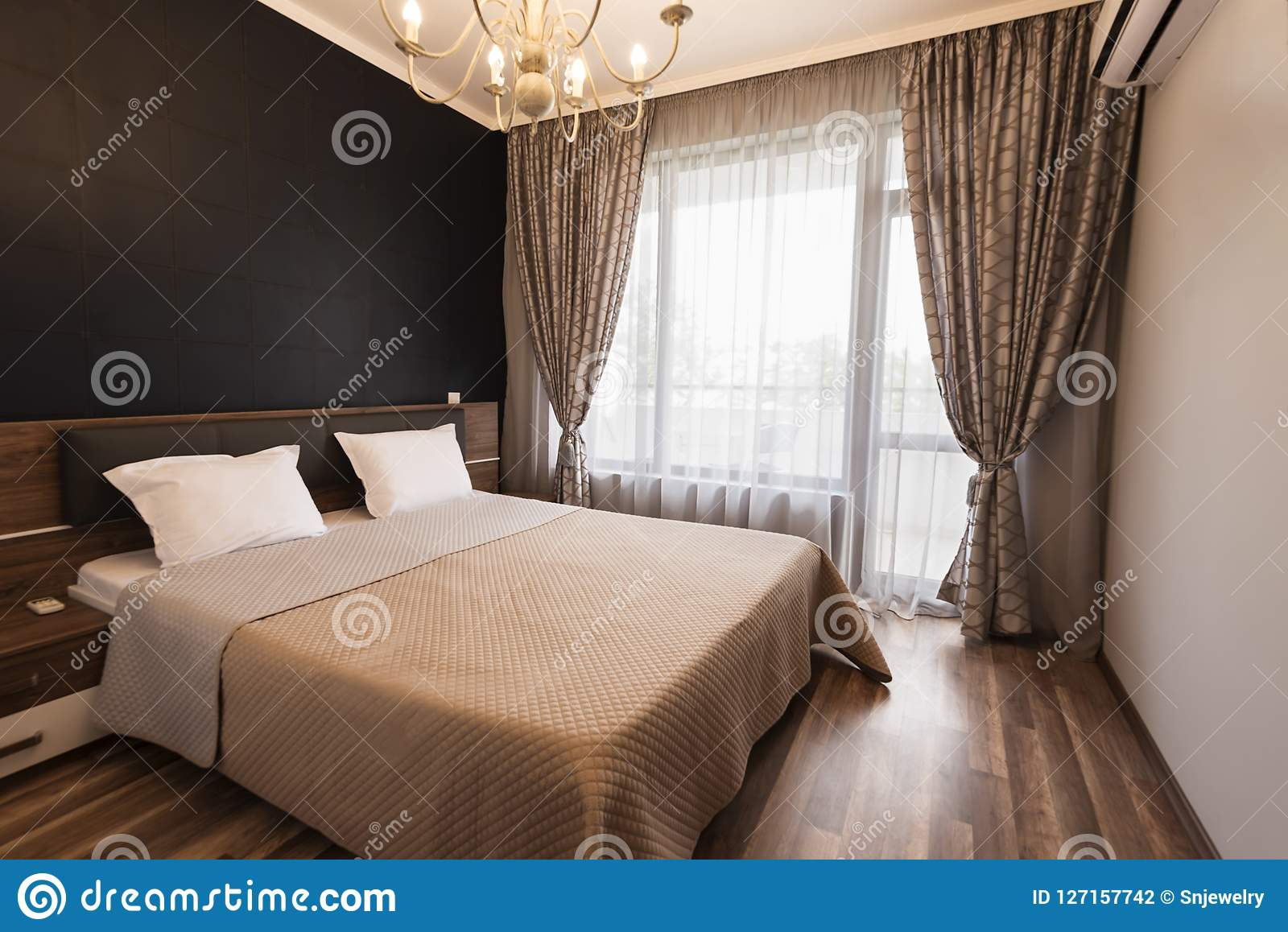 Modern slaapkamer binnenlands ontwerp De ruimte van het luxebed met bruine kleurentoon De vensters met lange gordijnen en wijkt a