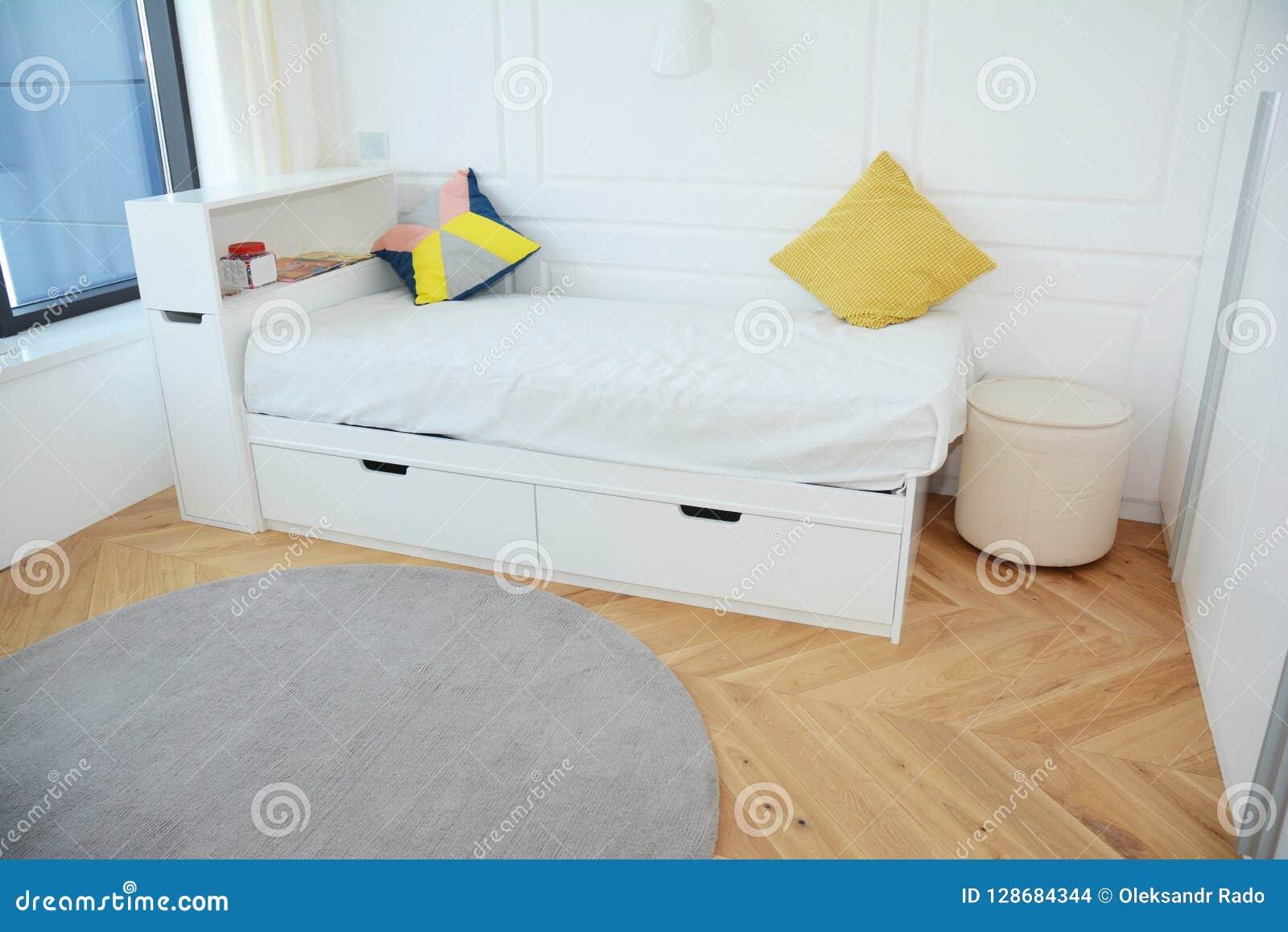 Modern slaapkamer binnenlands ontwerp met bed van het luxe het witte kind, eigentijds binnenlands ontwerp en comfortabel tapijt