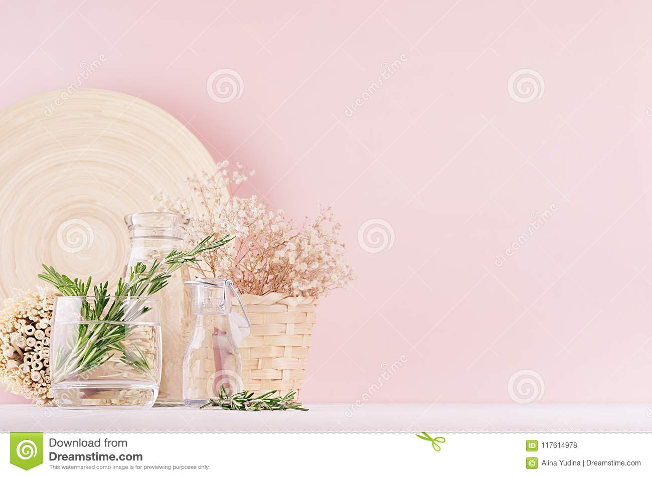 Modern soft light pink pastel home interior with green plant, dried white flowers, beige bamboo plate on white wood background.
