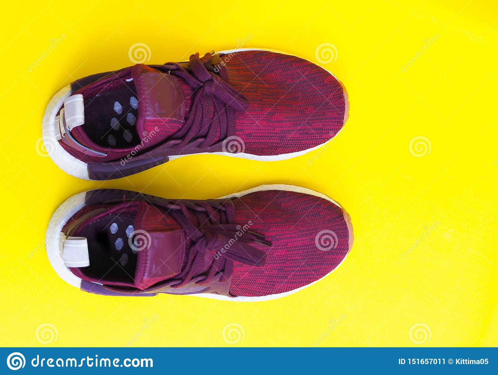 Modern red pair fashion sneakers isolated on yellow background