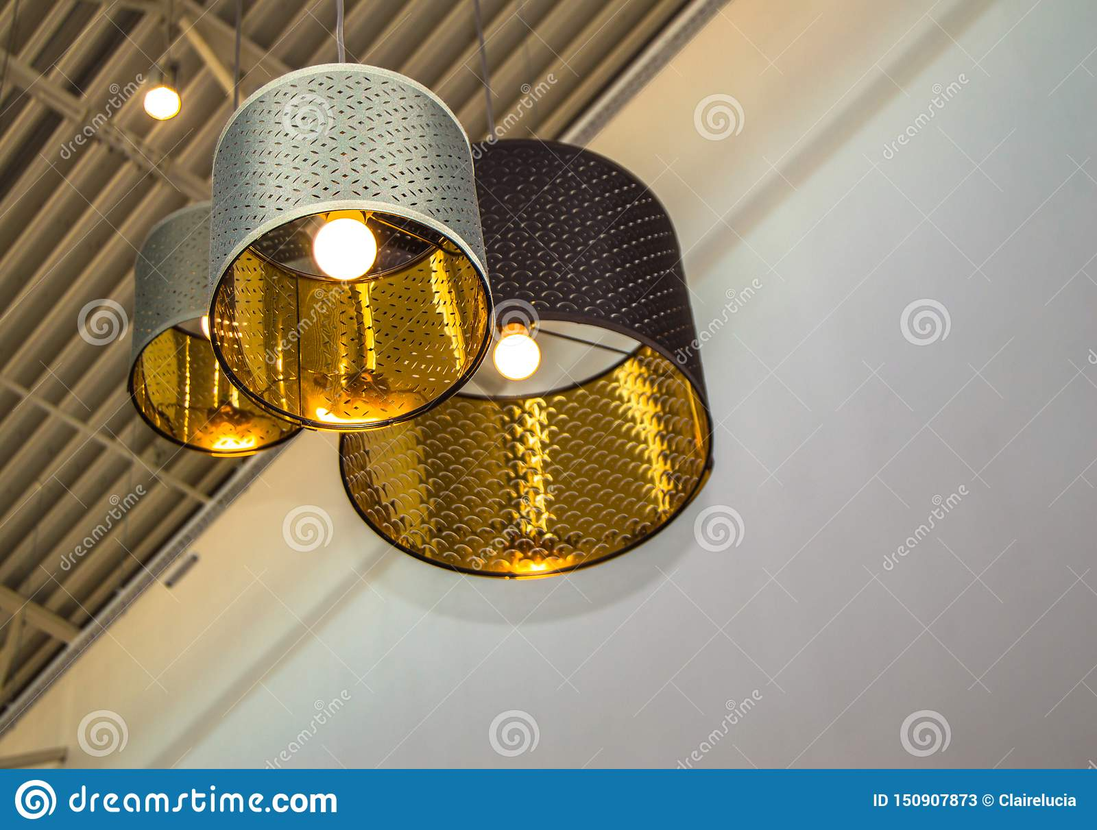 Modern style bronze decorative lamps and Golden lampshades hang on a long rope, industrial ceiling, interior design