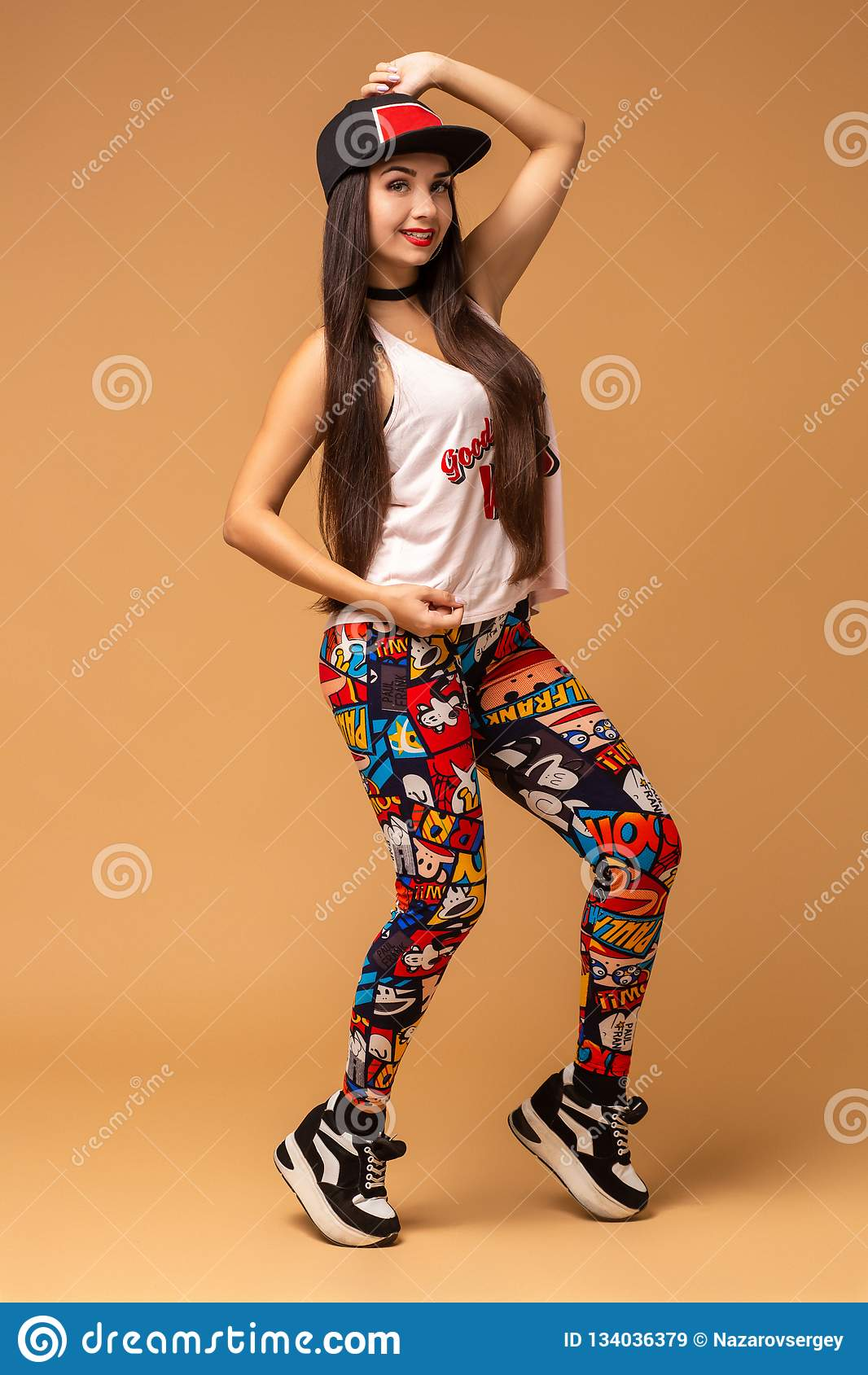 Modern style dancer posing on studio background. Hip hop, jazz funk, dancehall