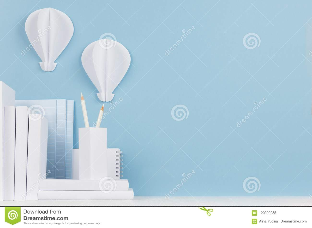 Modern style workplace - white stationery and decorative paper balloons on soft blue background and light desk.