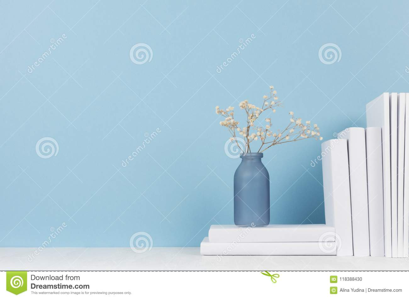 Modern style workplace - white stationery and glass vase with dry flowers on soft blue background and light desk.