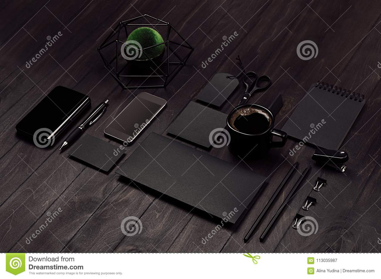 Modern stylish working place with blank black stationery, phone, coffee, green plant on dark wood board, inclined.