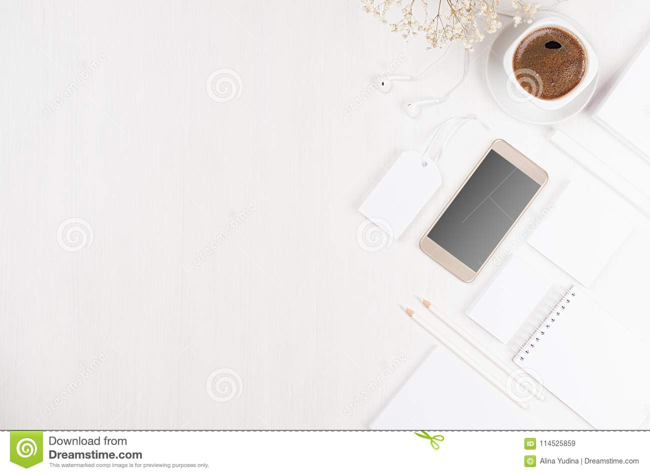 Modern stylish working place with blank white stationery, copy space, phone, coffee, flowers on soft white wood board.