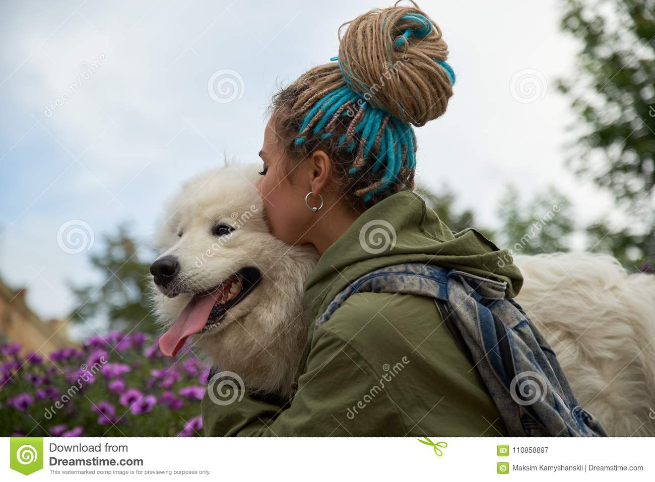 Modern stylish young girl with dreadlocks on her head hugs and kisses her beloved dog snow-white Samoyed.
