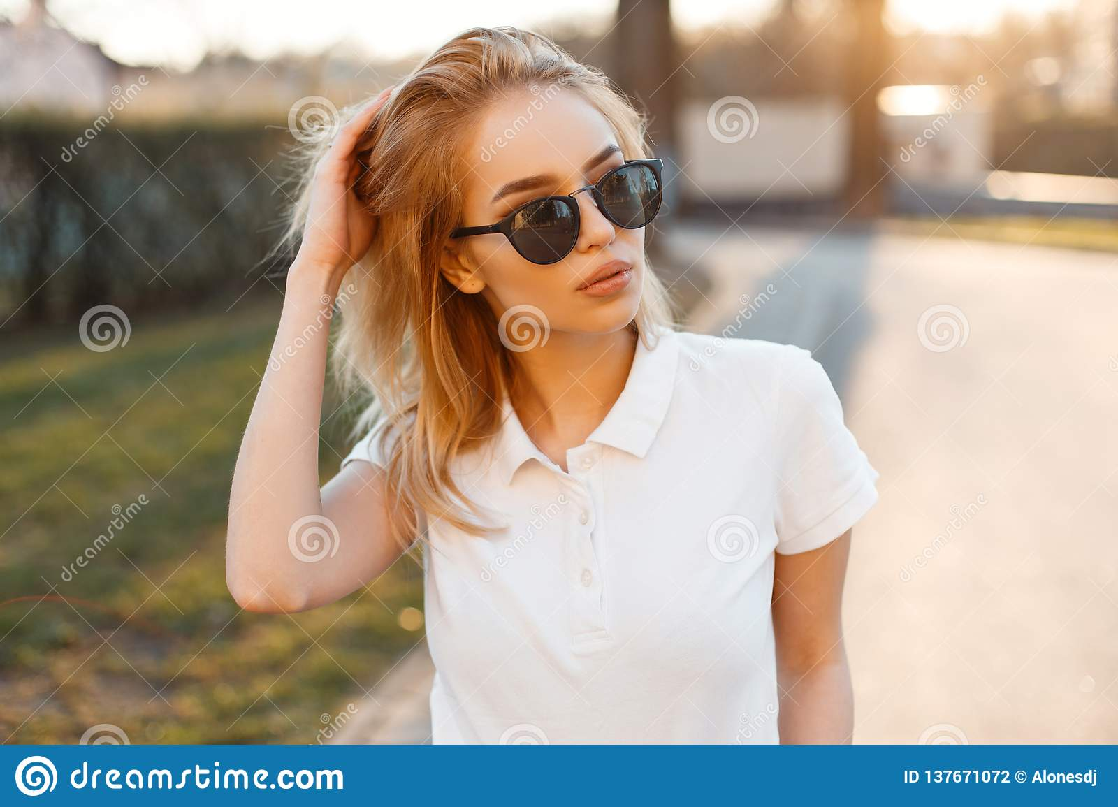 5bb5e7801874 Modern stylish young hipster woman in trendy white polo t-shirt in black  sunglasses stand