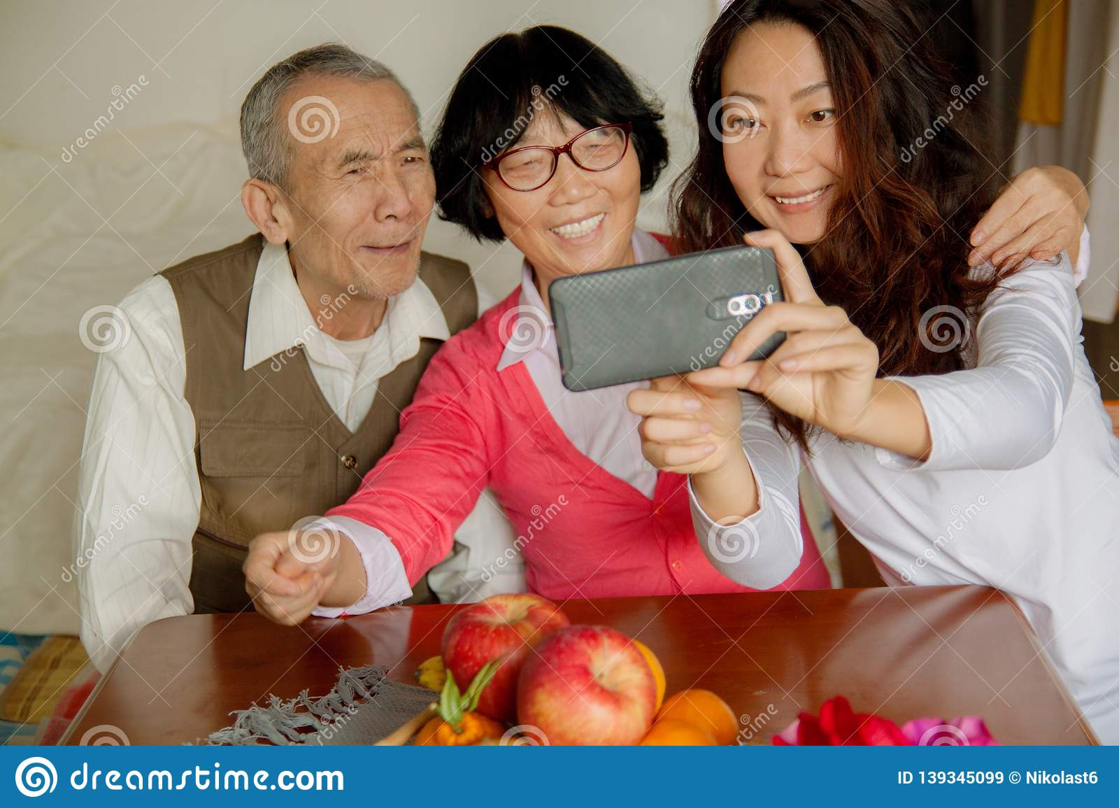 Daughter and senior parents using smartphone at home.