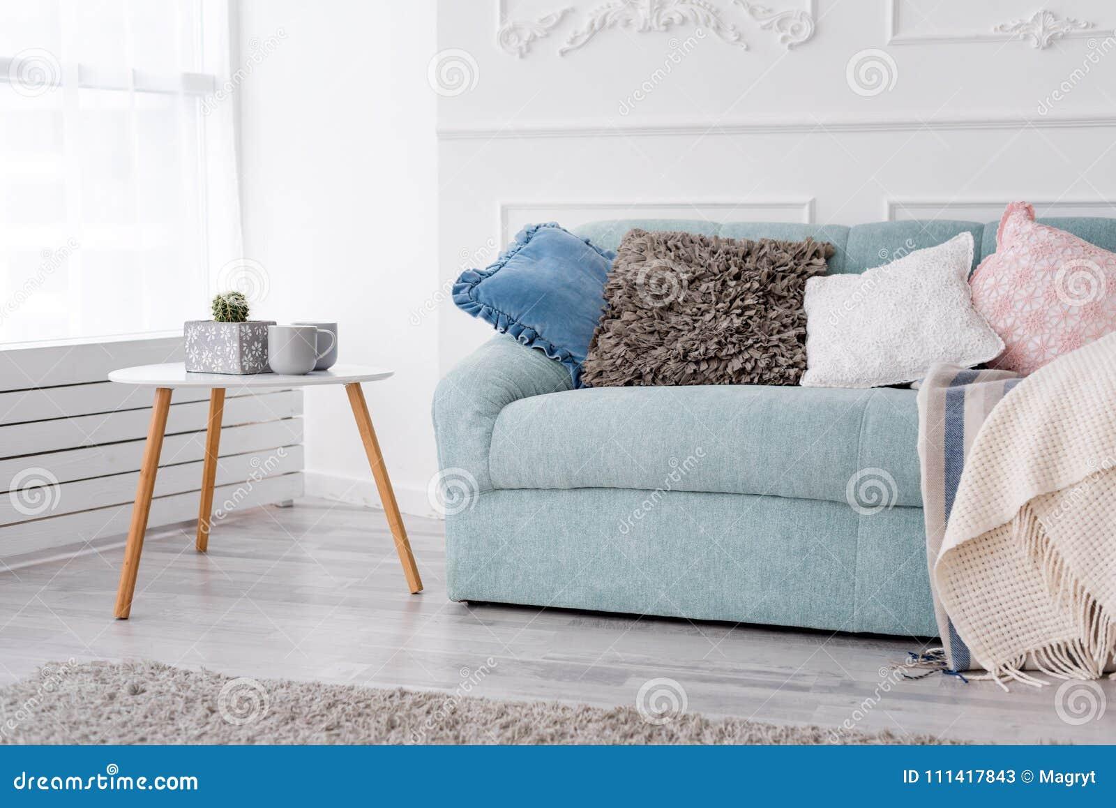 Modern träkaffetabell och slags tvåsittssoffasoffa med kuddar Vardagsruminre och enkelt modernt hem- dekorbegrepp
