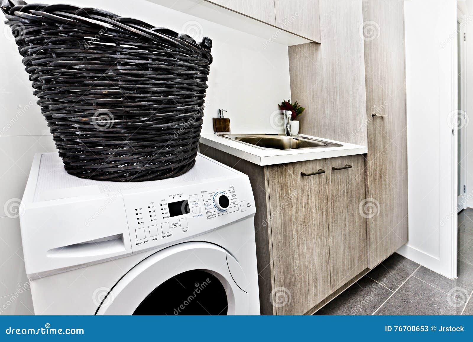 Modern tvättstuga med en tvagningmaskin och korg