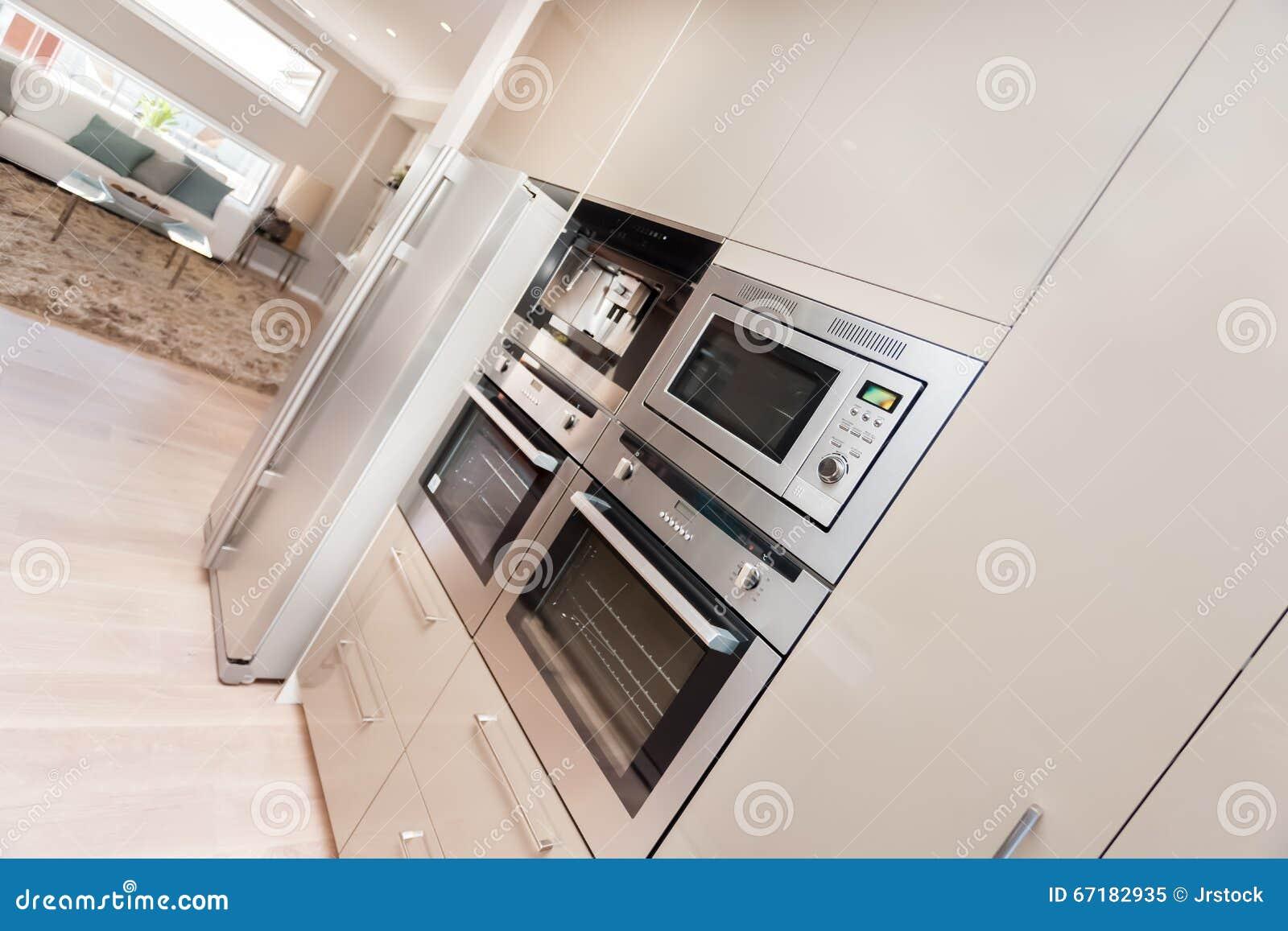 Modern ugn och kylskåp som fixas till väggen med skaffericupbo