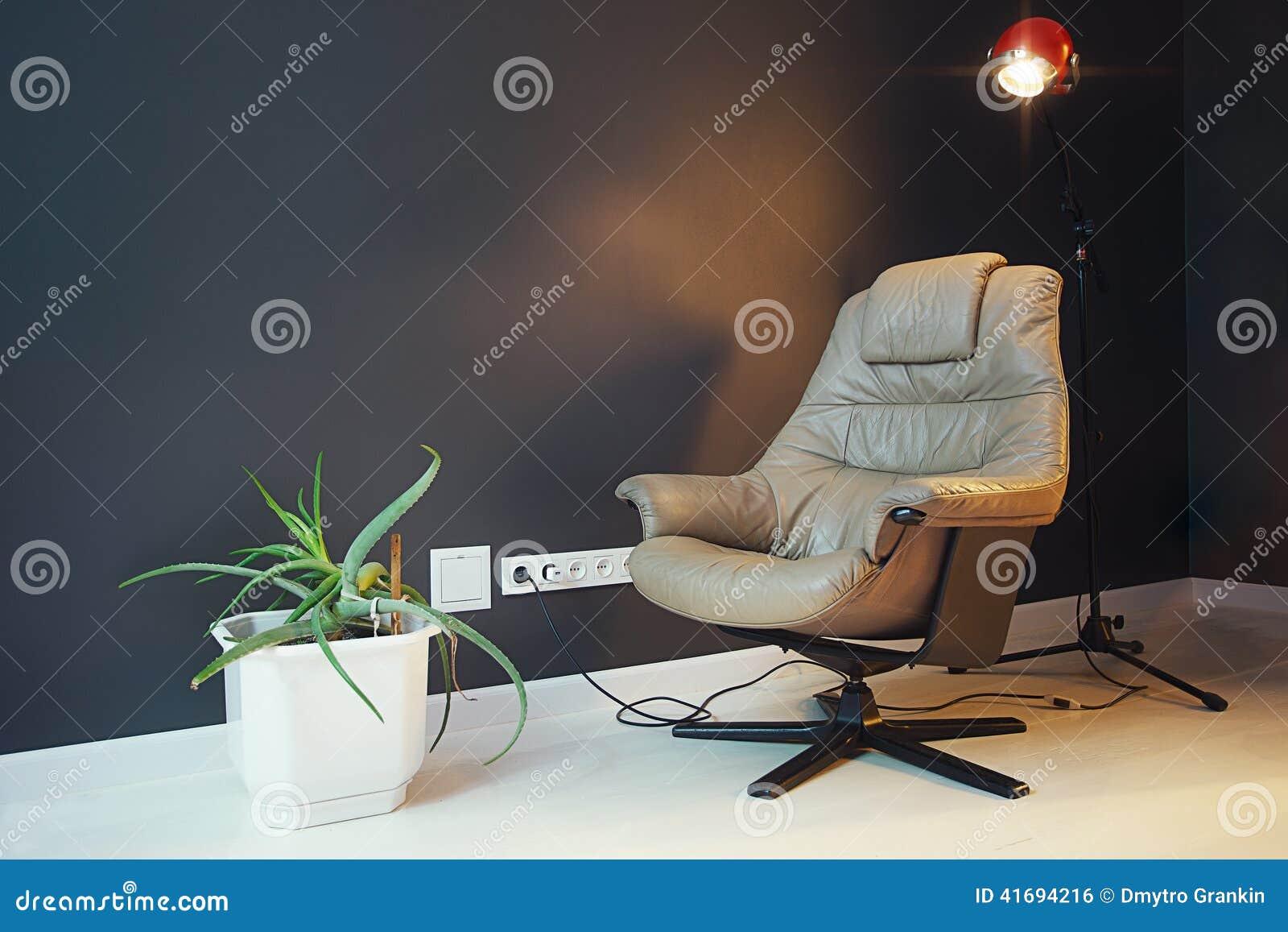 Modern vardagsrum med den beigea läderfåtöljen och svartväggen