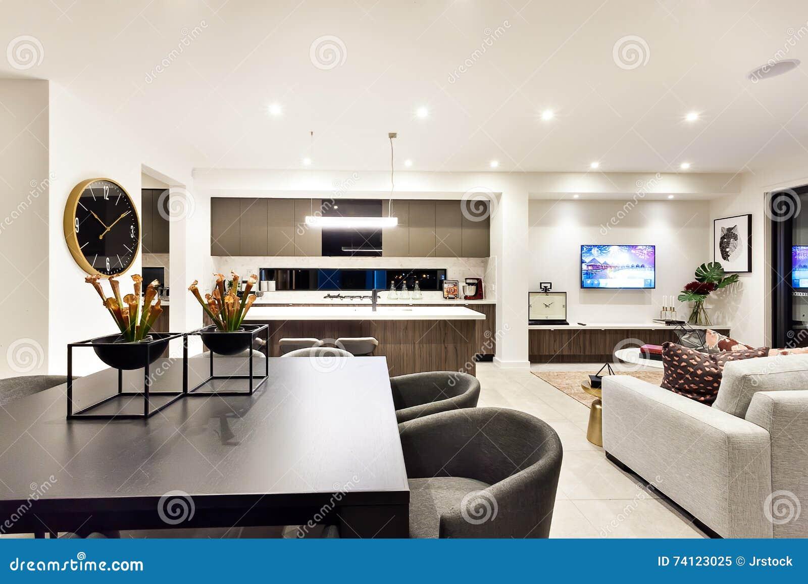 Modern vardagsrum med en television bredvid matställe och kök