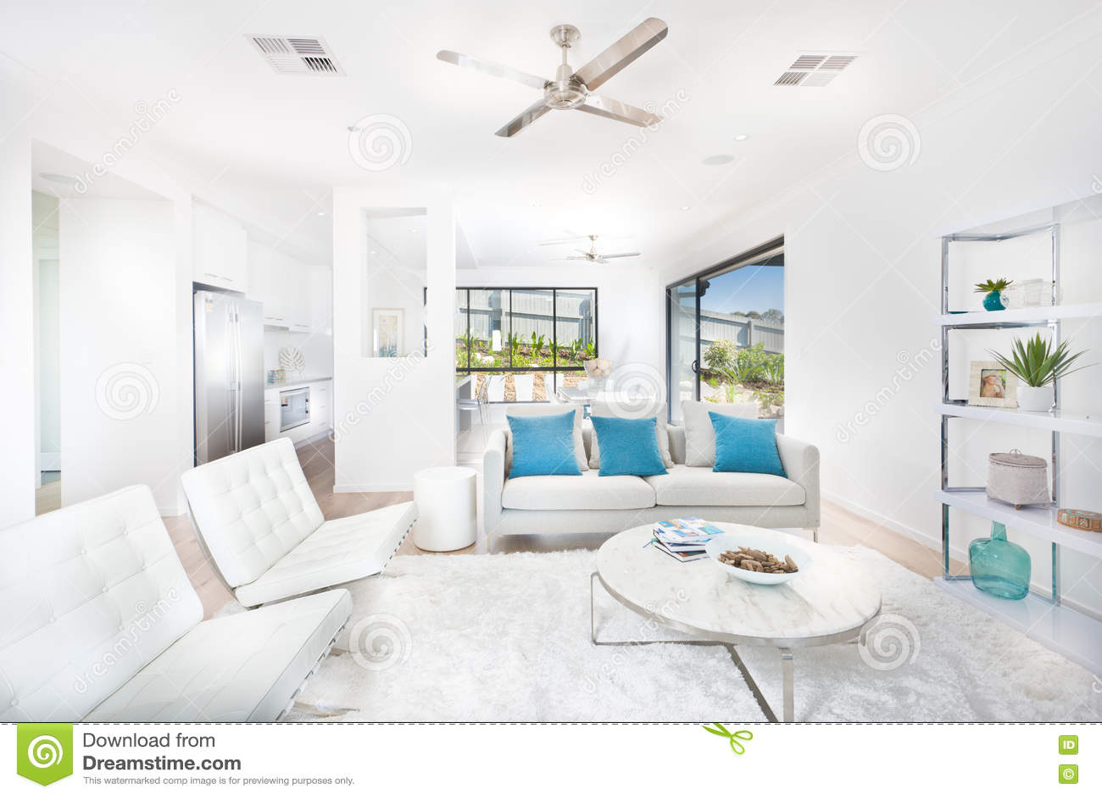 Modern vardagsrum med vita väggar som är upplysta med solljus