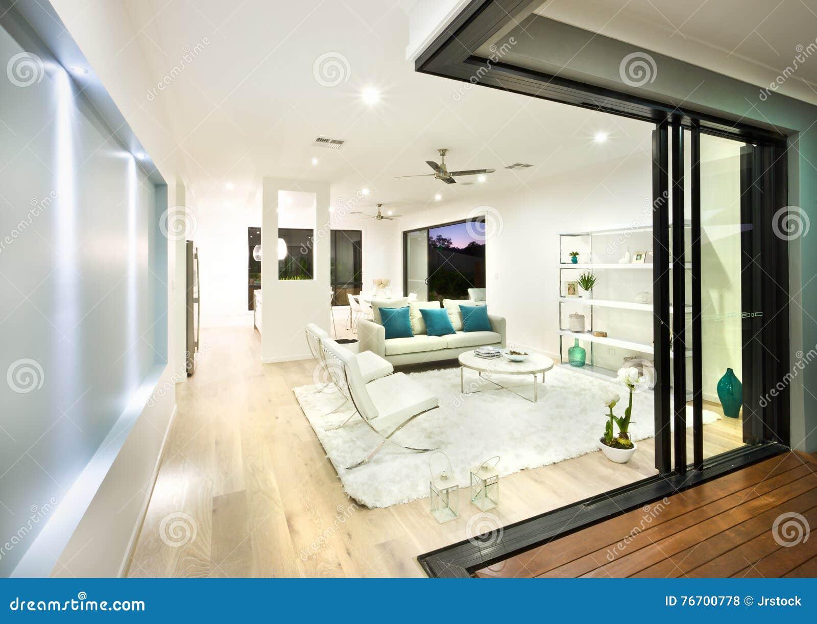 Modern vardagsrum som är upplyst på natten med ljus