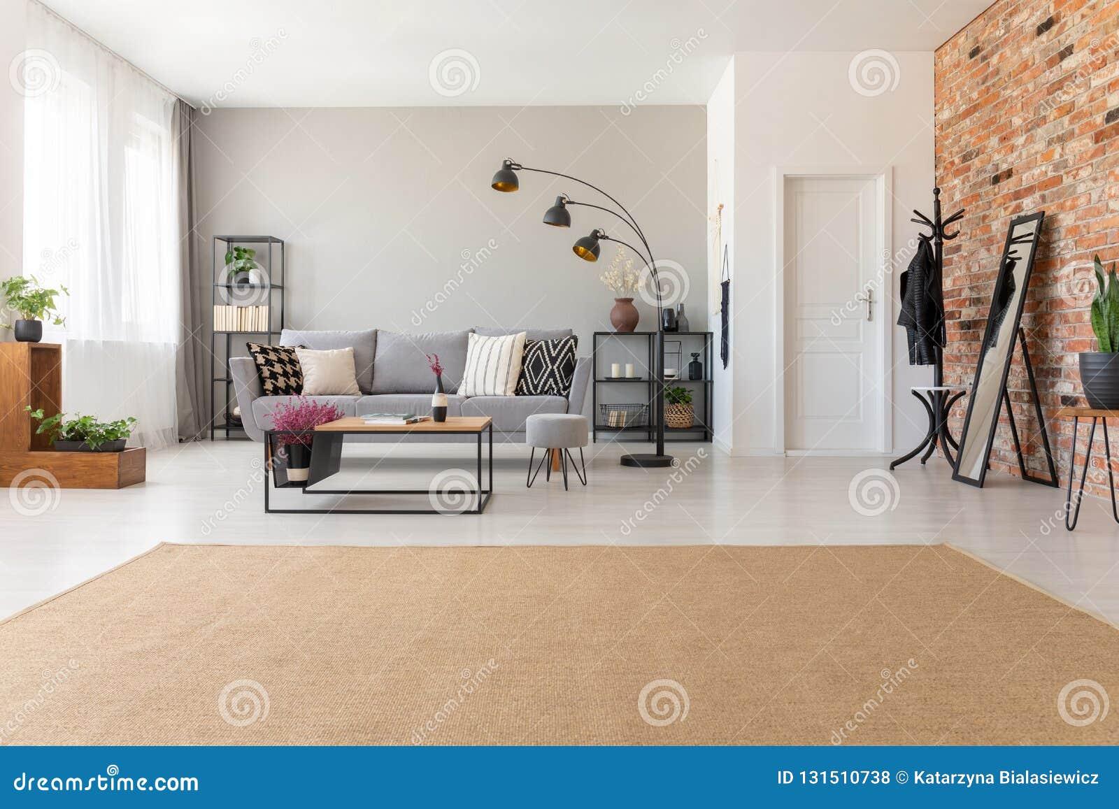 Modern vardagsruminre med den industriella möblemang- och tegelstenväggen, verkligt foto med kopieringsutrymme