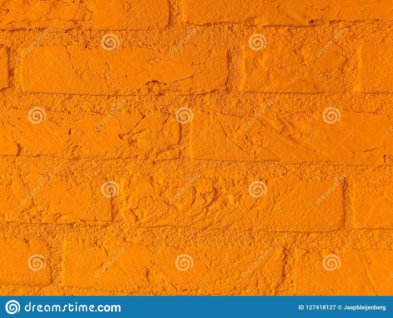 Modern vibrant orange stone brick wall with big bricks close up background pattern