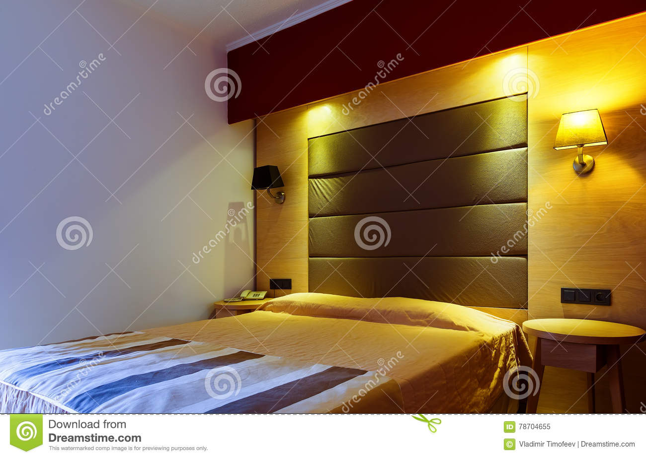 Modern, warm, inviting bedroom or hotel room. Light and shadows