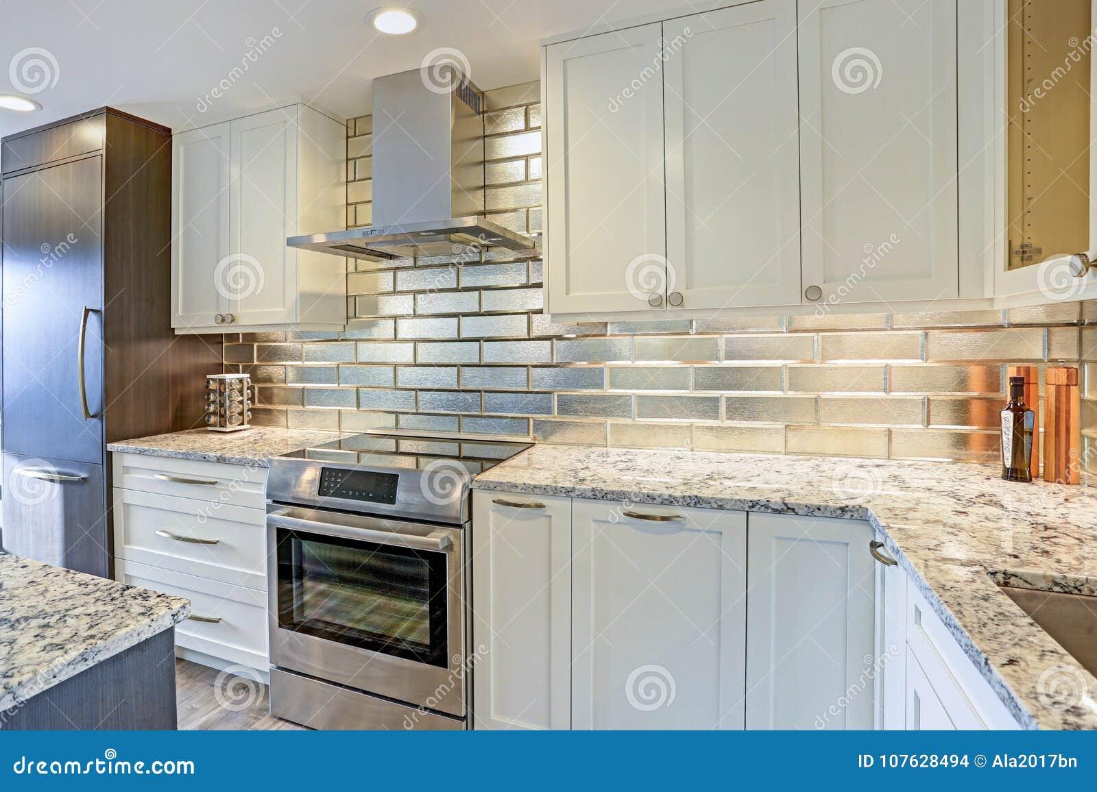 - Modern White Kitchen Design With Silver Backsplash Stock Photo