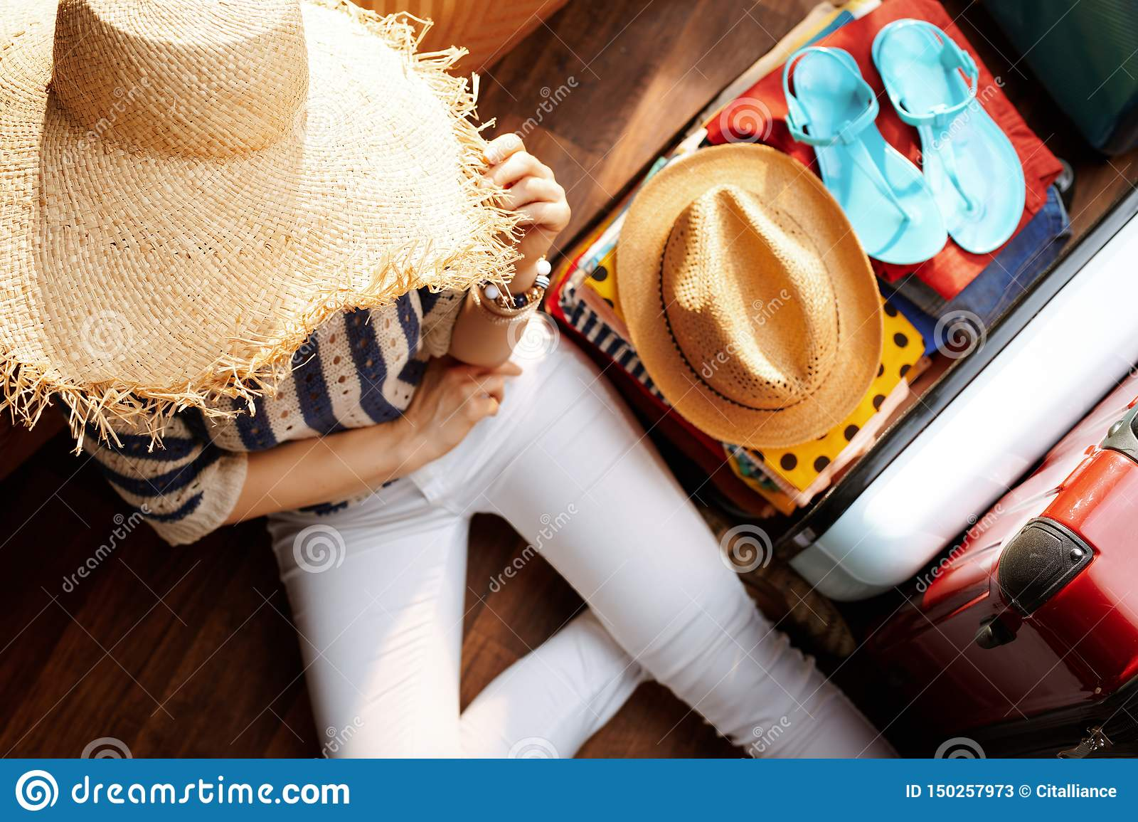 Modern woman with big summer hat planning summer vacation