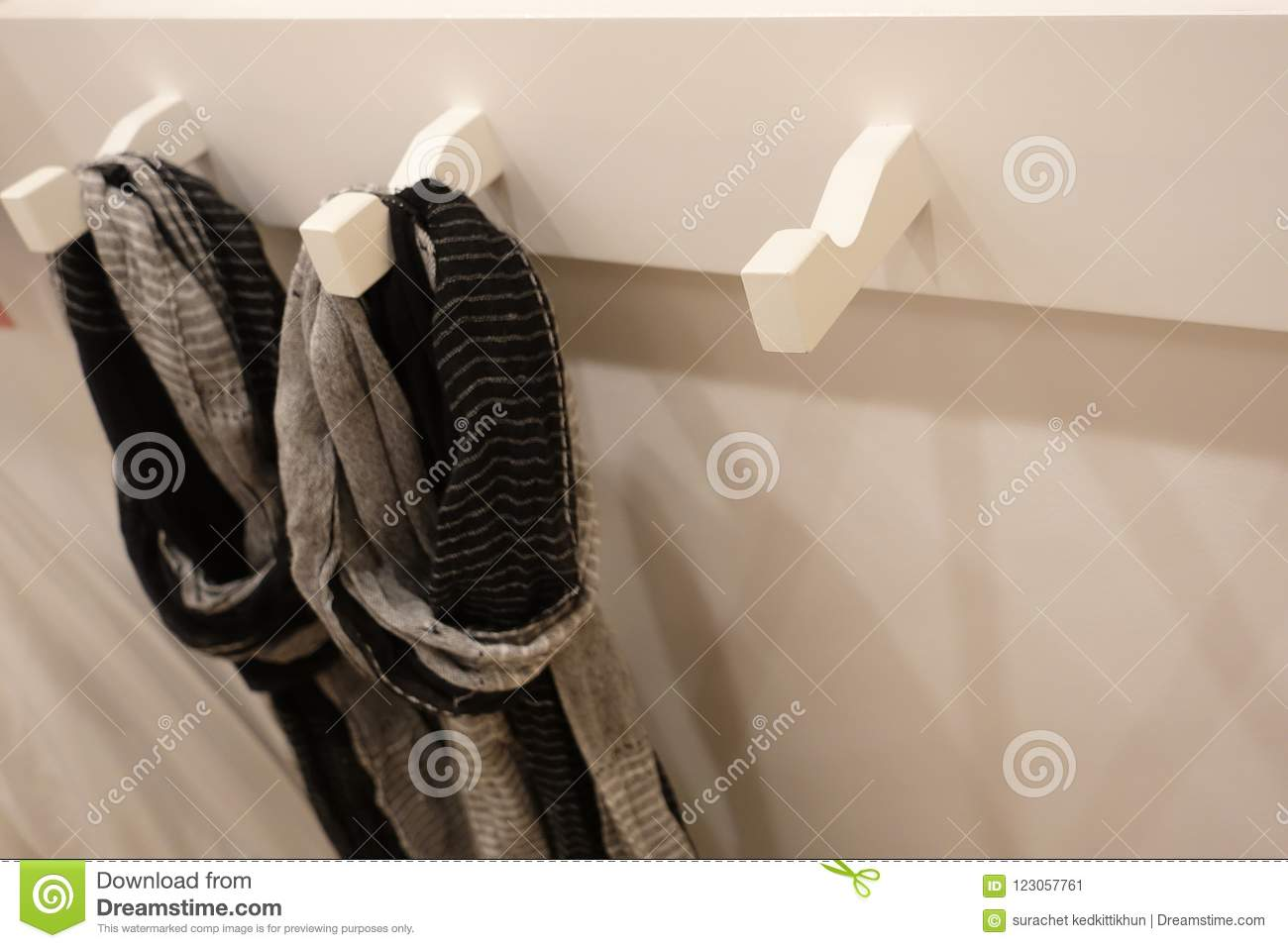 Modern wooden wardrobe with clothes hanging on rail in walk in closet,. Choice of fashion clothes of different colors on wooden hangers Stock Image