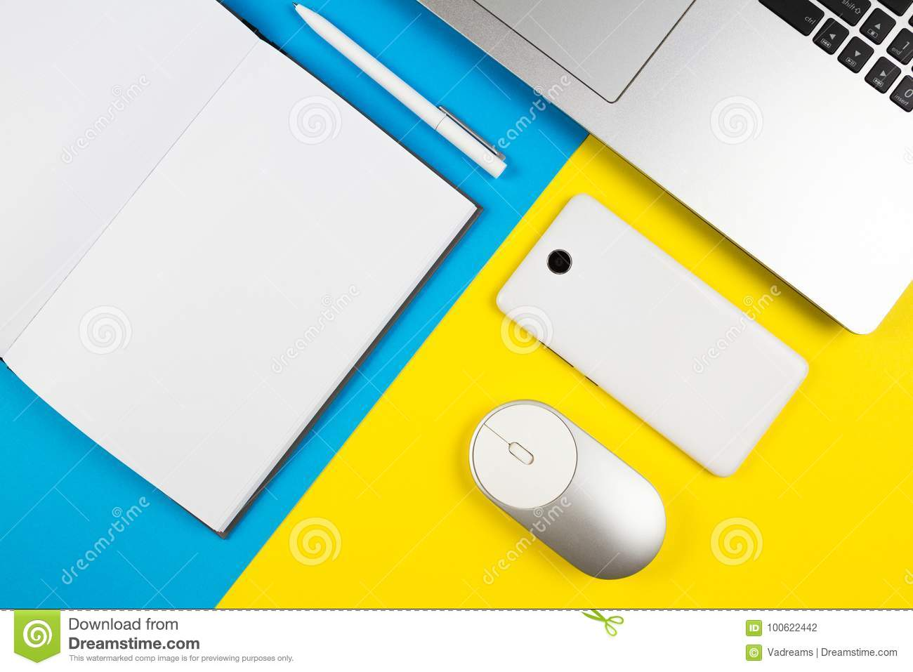 Modern workplace with notebook, computer mouse, mobile phone and white pen on blue and yellow color background