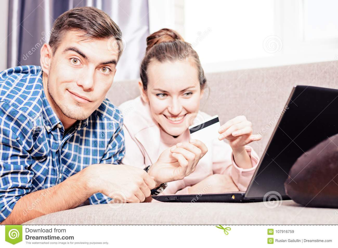 Modern young family makes purchases online Leda on sofa using a laptop, payment by credit card. Emotional face