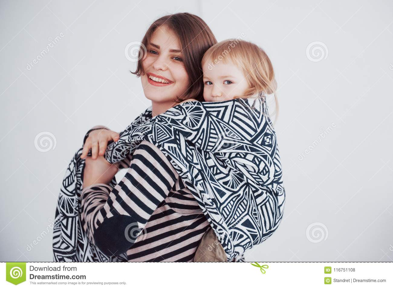 Young Mother Carrying Baby Boy Sitting In Sling Stock