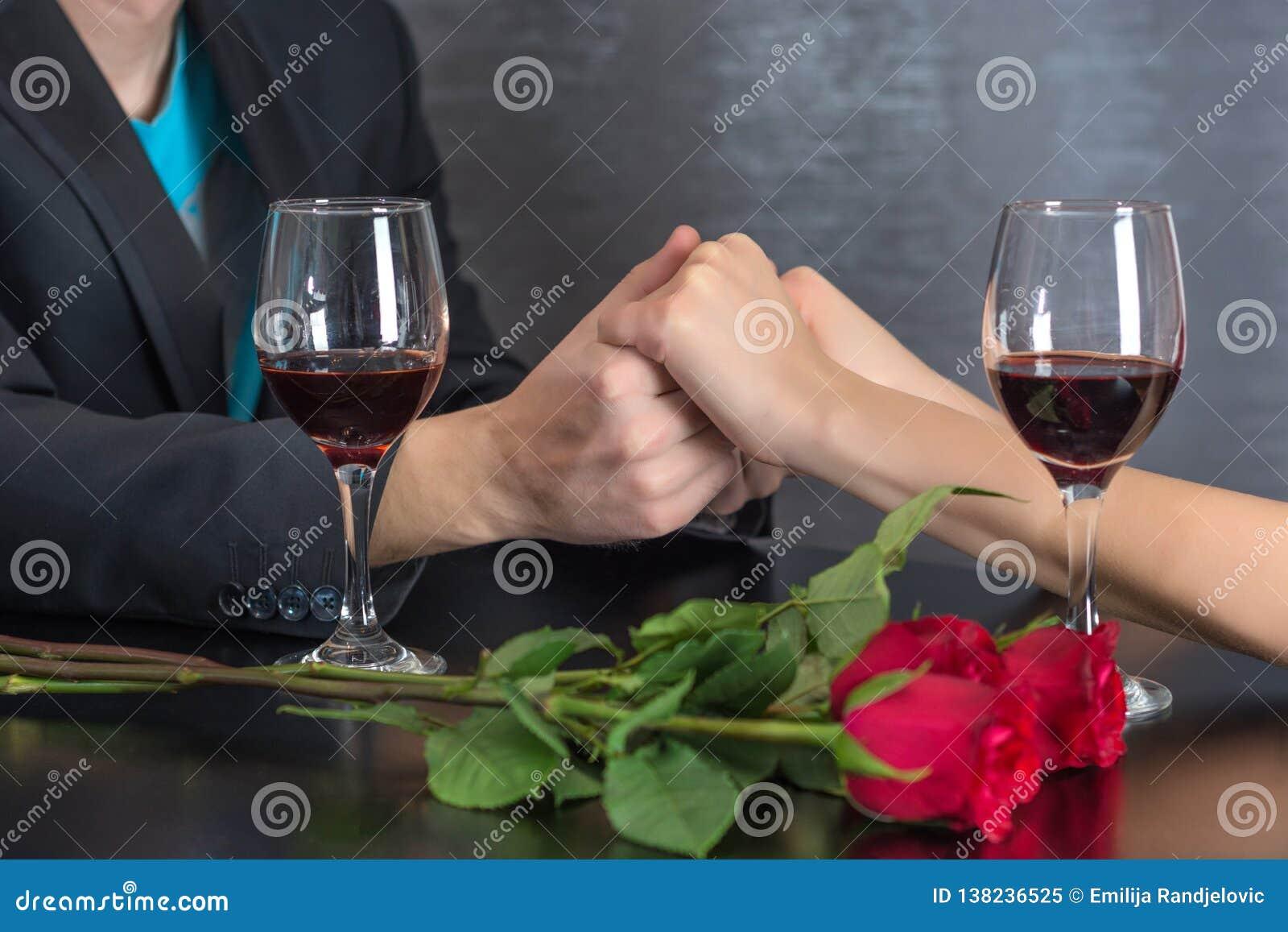 Moderna parhänder på restaurangtabellen med två exponeringsglas av rött vin och rosor