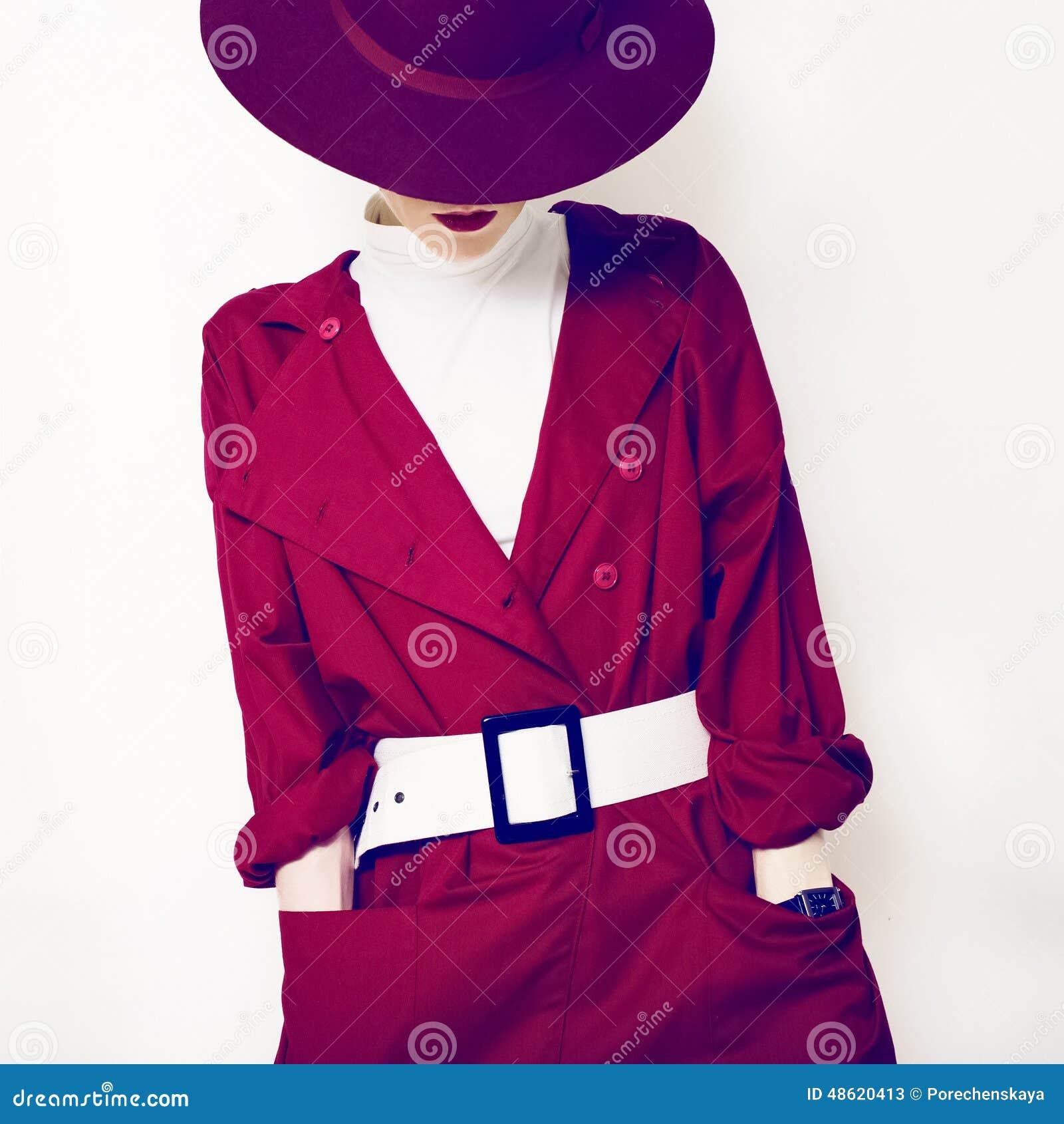 Moderne Art schöner Weinlesedame in einem roten Mantel und in einem Hut