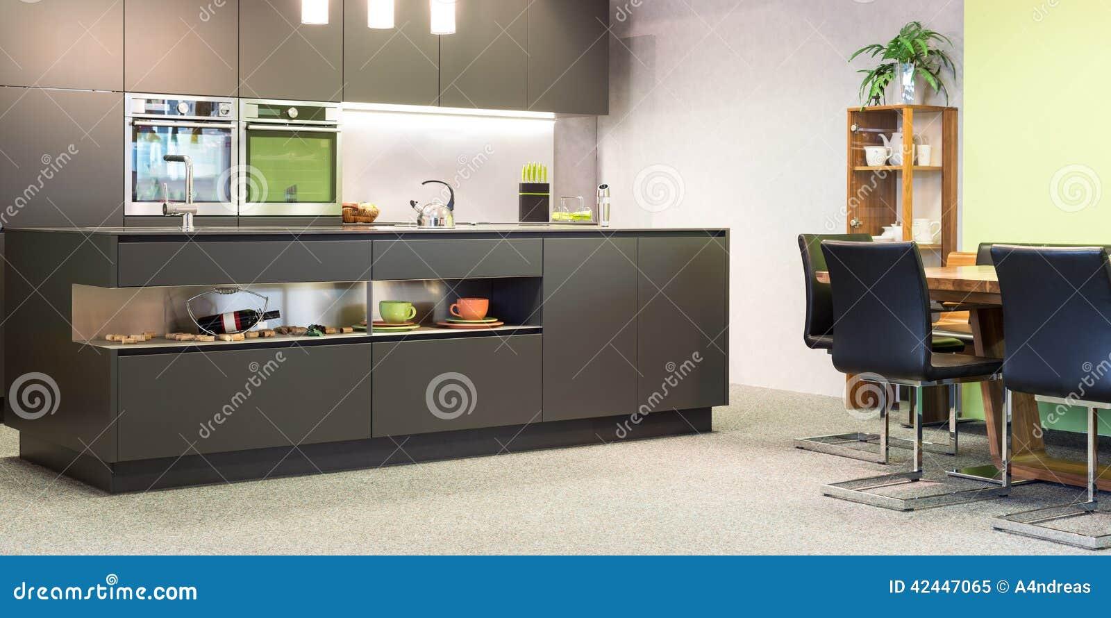 Moderne donkere grijze keuken met verlichting stock afbeelding