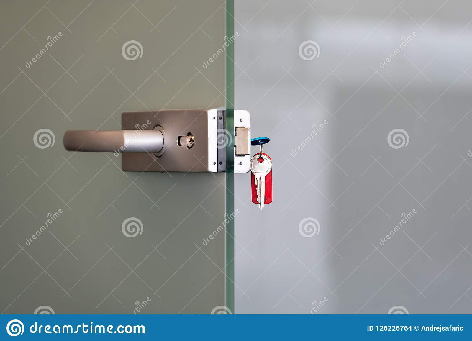 Moderne glasdeur met de handvatten van de metaallegering en zeer belangrijke ketting in slot, huis of het concept van de bureauve
