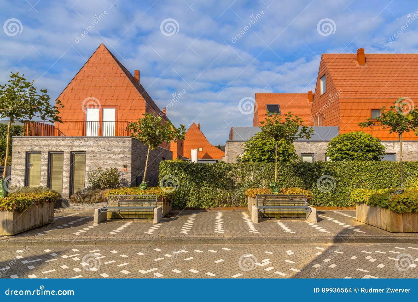 Moderne huizen met de conspicious rode tegels van het leidak stock