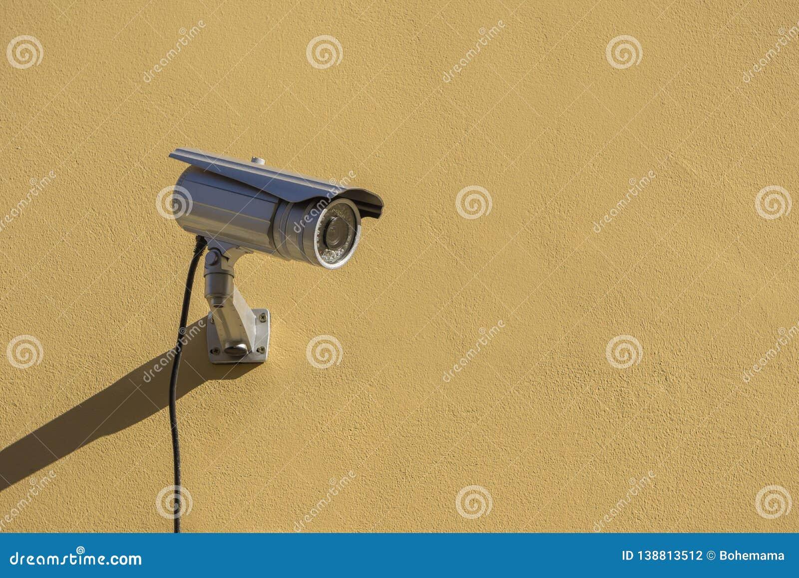 Moderne kabeltelevisie-camera op gele de bouwmuur