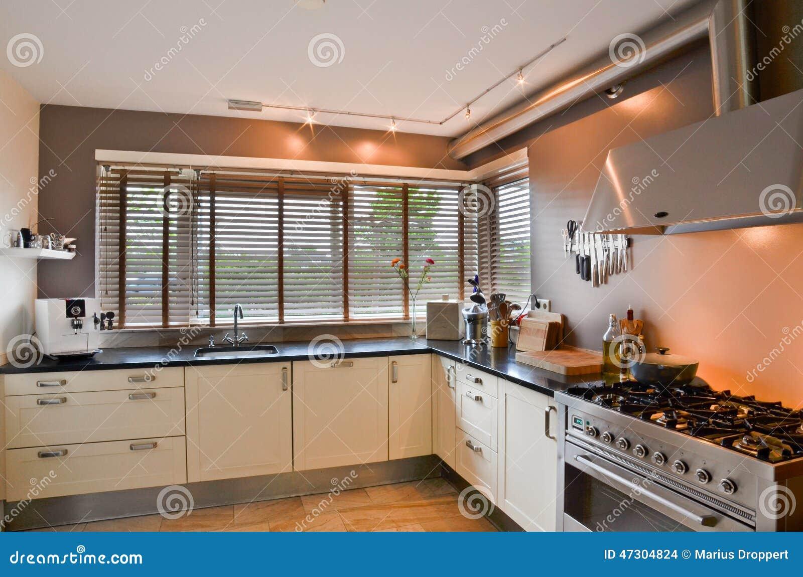 Voorraadkast Keuken Inhoud : Moderne keuken met roestvrij fornuis en houten vloer met venster op de